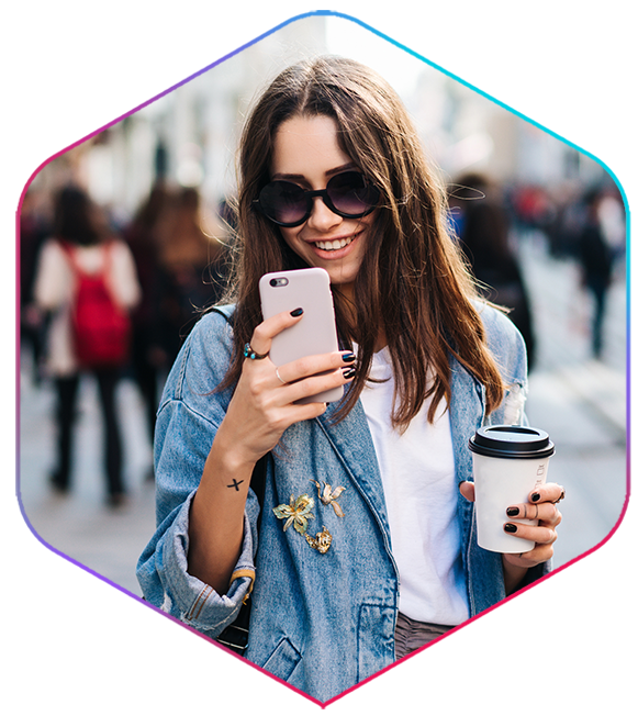 girl looking at iPhone with coffee cup in hand