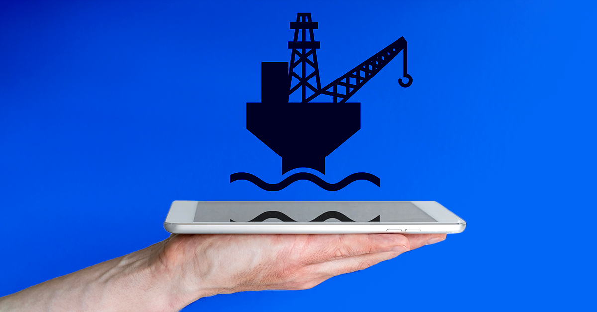 hand holding ipad with oil rig over the top